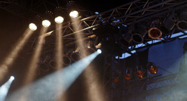Un-gelled spotlights hanging from a gantry.